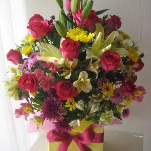 Caja de regalo amarilla con rosas fiusha